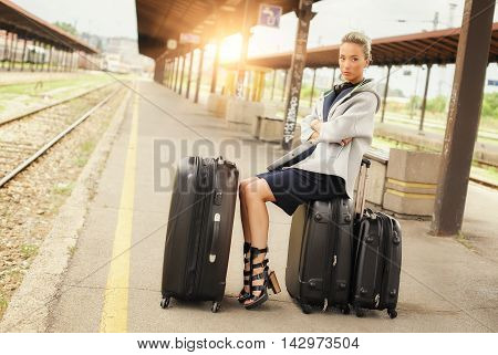 Elegant Woman Sitting On Suitcases And Waiting For The Train