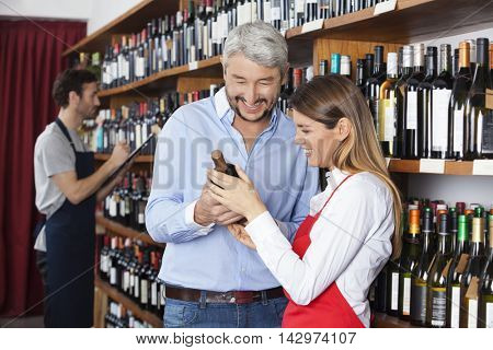 Customer And Saleswoman Looking At Red Wine Bottle