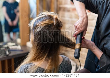 Professional hairdresser using curling iron. Hair curls in salon people at work