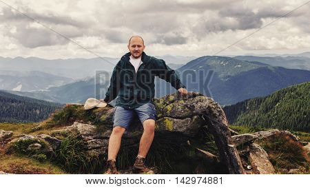Portrait of young men tourist who stopped to the rest in Carpathian mountains summertime journey travel concept