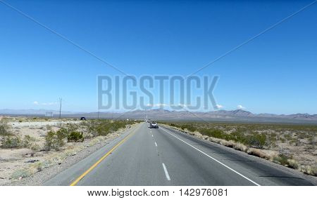 Long, straight highway through the Mojave Desert in California, United States of America, two-lane roadway with marking and emergency lane, mountainous landscape and blue sky
