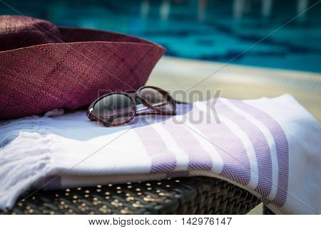 Concept of summer accessories close-up of white and purple Turkish towel, sunglass and straw hat on rattan lounger with blue swimming pool as background.