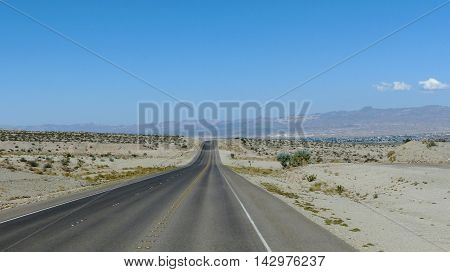 Long, straight highway through the Mojave Desert in Nevada, United States of America, three-lane roadway with marking and emergency lane, mountainous landscape and blue sky