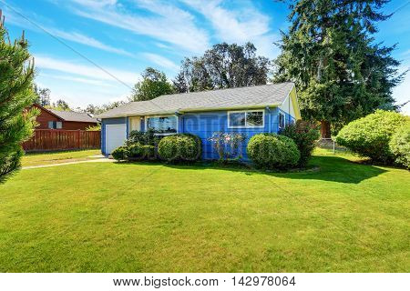 Small Cute Blue House With Well Kept Lawn And Trimmed Hedges.