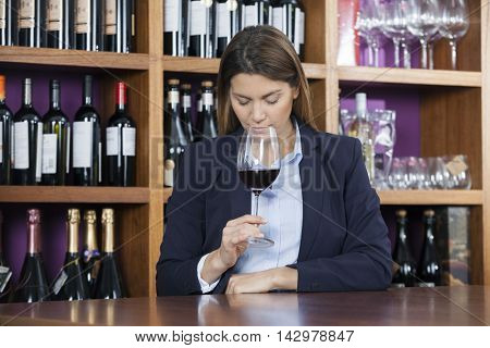 Customer Smelling Red Wine At Counter In Shop