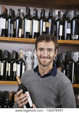 Happy Customer Holding Wine Bottle In Supermarket
