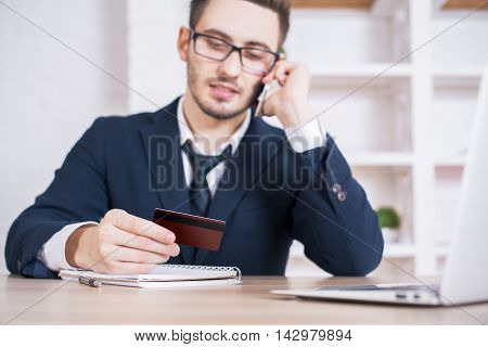 Businessman in office holding credit card and placing an order by phone