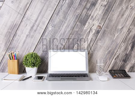 Front view of creative designer desktop with blank white laptop smartphone calculator plant stationery items water glass and other items. Mock up