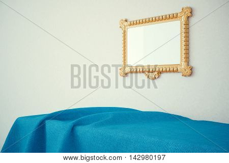Ornate golden picture frame hanging above surface covered with blue cloth on concrete wall background. Mock up 3D Rendering
