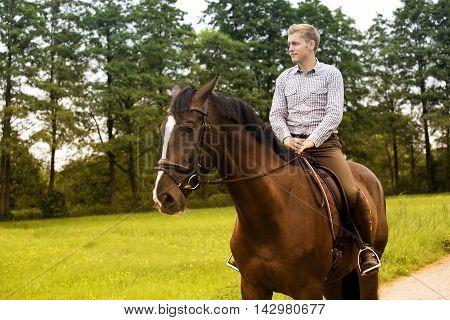 man riding his brown horse on farmland