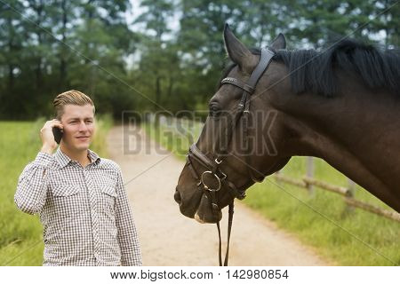 man talking on phone standing next to his brown horse in nature