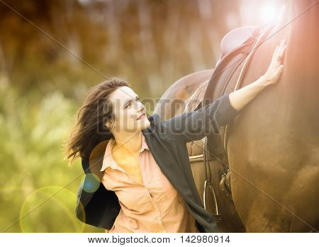young woman and her brown horse in nature