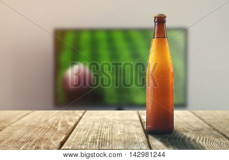 Unlabeled beer bottle on wooden table in front of television show of football. Watching football match at home.