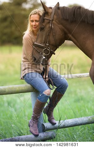 blond woman with her brown horse on farmland