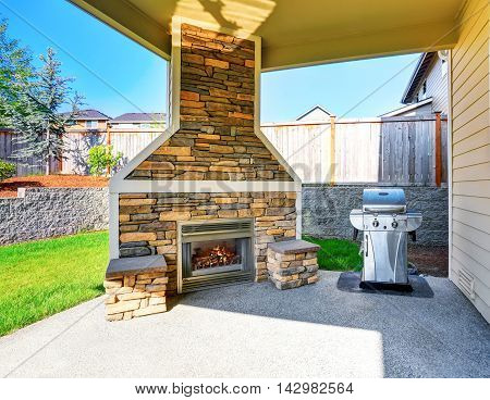 Cozy Covered Patio Interior With Stone Trim Fireplace And Barbecue.