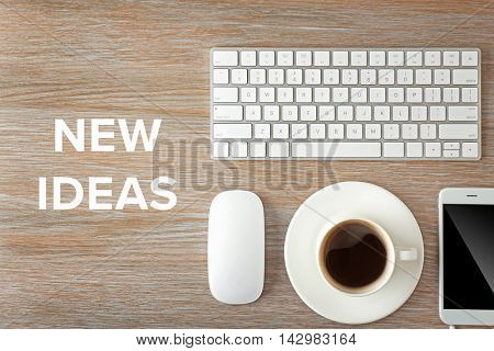 Business training concept. Keyboard, phone and cup of coffee on a wooden desk background, top view