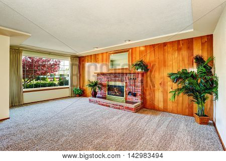 Empty Living  Room With Wood Panel Wall And Fireplace