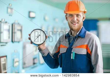 Young Happy Engineer Holding Measurement Equipment In Control Room