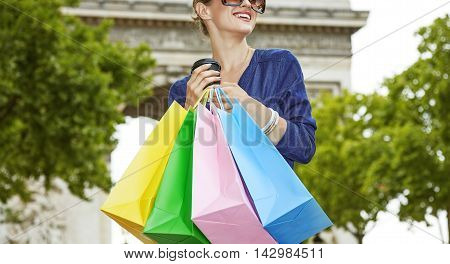 Woman With Shopping Bags And Cup Of Coffee Looking Into Distance
