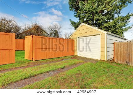 Small Beige Detached Garage At The Fenced Backyard