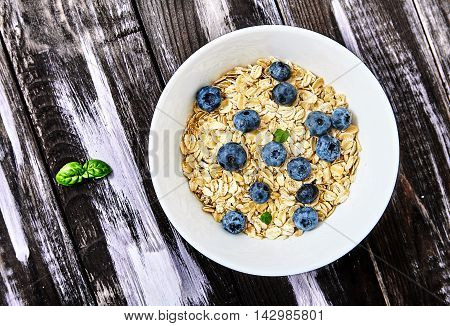 Top view shot of raw oat flakes topped fresh blueberries and basil leaves in white bowl. Dietary food on dark wood back with basil or mint near it. Perfect ingredients for healthy delicious breakfast.