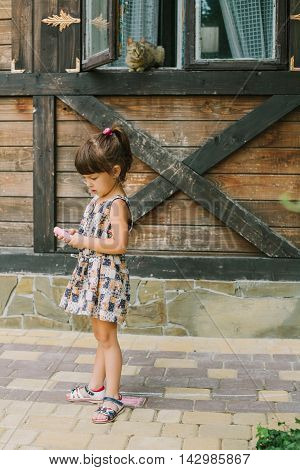 girl standing with chalk near a wooden house. kitty in a window