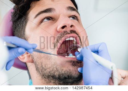 Young man having teeth professionally cleaned, color image, horizontal image