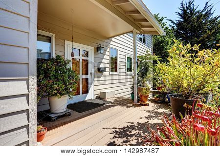 Nice Wooden Floor Porch With Flowers And Bushes Around. Front White Entry Door.