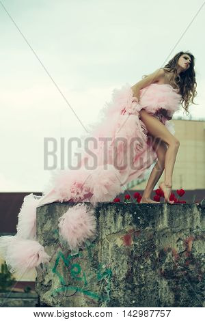 Glamour young woman with pretty face in pink dress on stony parapet with red tulips outdoor