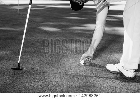 Golfer picking ball up after placing the marker behind, black and white image