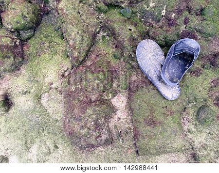 A shot of a pair of sand covered pool shoes on the rocks of a beach