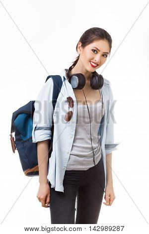 Portrait of happy teenager girl with school backpack and earphones isolated on white background. Happy woman in casual clothing. Good for sports and travel concept