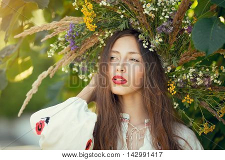 Smily portrait of beautiful girl in wreath of flowers in meadow on sunny day. Portrait of Young beautiful woman wearing a wreath of wild flowers. Young Slavic girl