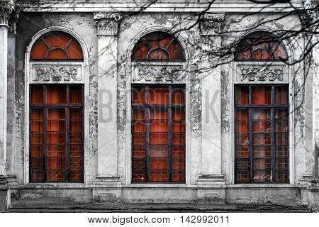 Facade of old abandoned building with three large arched windows of the red glass. Monochrome background