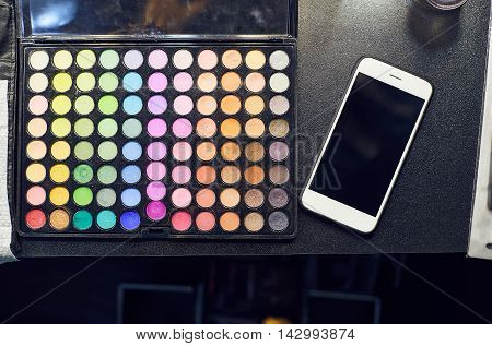 Close up eye shadows palette make up process. Set of professional colorful eyeshadow palette in close-up view with white mobile phone on black table.