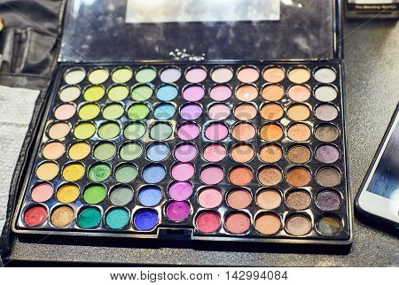 Professional multicolour eyeshadows palette, close up on black background. Beauty creative assortment of palettes with rich and deep colors of lipstick and eyeshadows.