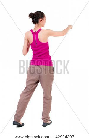 back view of woman funny fights waving his arms and legs. Rear view people collection. backside view of person.  Isolated over white background. dark-skinned girl in a red t-shirt boxing.