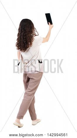 back view of standing young beautiful  woman  using a mobile phone. girl  watching. Rear view people collection.  backside view of person.  Isolated over white background. Long-haired curly girl