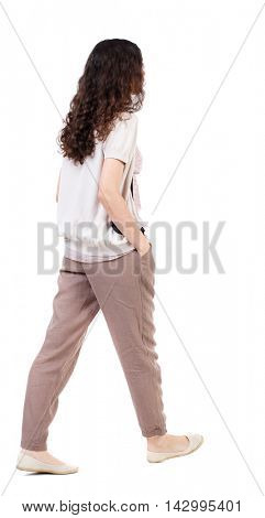 back view of walking  curly woman.  backside view of person.  Rear view people collection. Isolated over white background.Long-haired curly girl walks slowly to the side with his hands in his pockets.