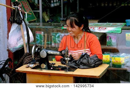 Ao Ping China - September 14 2006: Seamstress working with an old-fashioned sewing machine making clothing