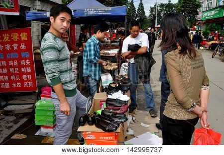 Ao Ping China - September 14 2006: Man selling shoes at the expansive outdoor Ao Ping marketplace