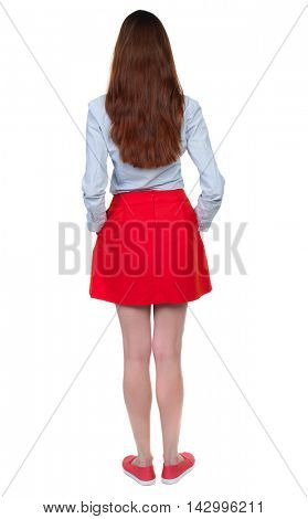 back view of standing young beautiful  woman.  girl  watching. Rear view people collection.  backside view of person. Long-haired brunette in red skirt standing with his hands in his pockets.
