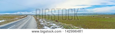 Panorama of green fields with the snowbound Hasan volcano on the distance Cappadocia Turkey.
