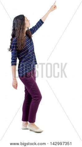 back view of walking  woman. beautiful redhead girl pointing.  backside view of person.  Rear view people collection. Isolated over white background. Long-haired curly girl is sad side considering