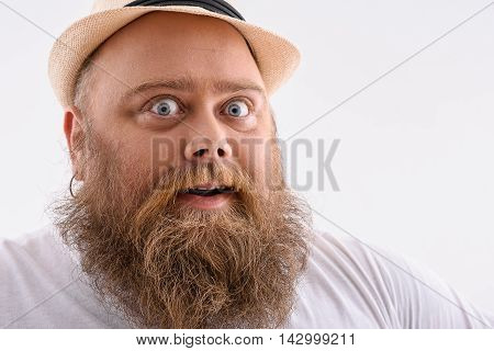 Thick man is looking at camera with surprise. He has hat and beard. Isolated