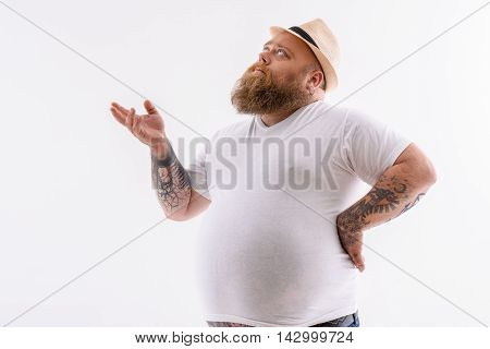 Thick bearded man is making serious decision. He is standing and gesturing. Fatty is looking up pensively. Isolated