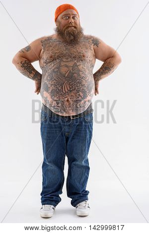 Fat man is standing with arms akimbo. He is looking at camera with surprise. Guy has big naked belly and beard. Isolated