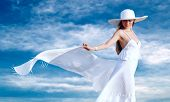 Young beautiful women in the white with pareo on the blue sky background poster