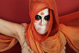 stock photo of wraith  - Woman in an orange scarf and wraith makeup - JPG