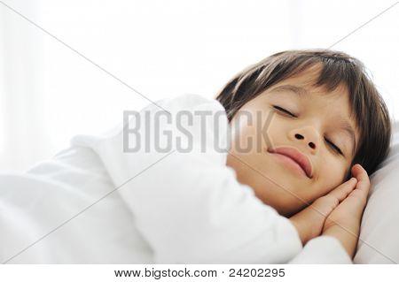 Cabrito en dormir en cama, feliz dormir en el dormitorio blanco